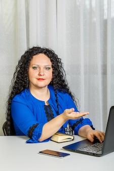 巻き毛のブルネットの女性は、スマートフォンで作業しているオフィスのテーブルに座っています