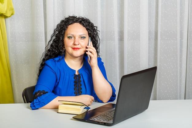 곱슬 갈색 머리 여자는 전화 통화하는 사무실에서 테이블에 앉아있다. 가로 사진