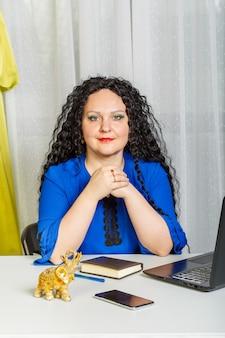 巻き毛のブルネットの女性は、ラップトップを持ってオフィスのテーブルに座っています