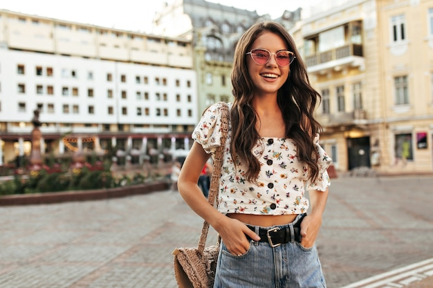Curly brunette woman in stylish jeans and trendy floral blouse smiles outside