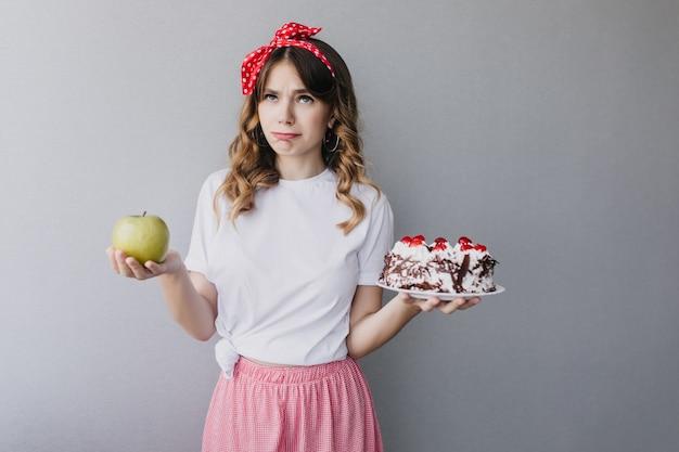 Кудрявая кавказская девушка думает о своей диете. внутренний снимок задумчивой чудесной дамы, держащей зеленое яблоко и сливочный торт.