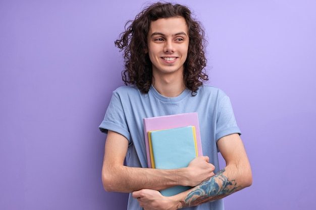 Curly caucasian guy with books in casual t-shirt posing isolated on purple wall background in studio