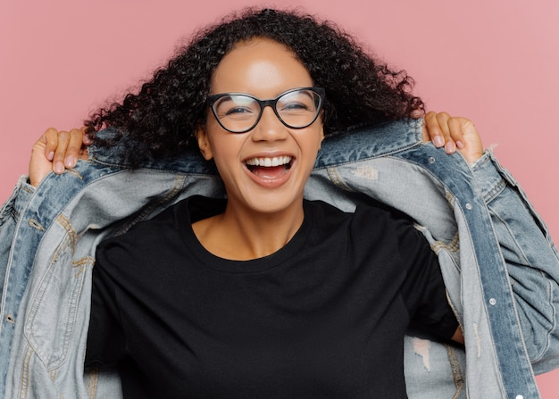 Curly cheerful woman tries on new denim jacket, wears optical glasses, smiles broadly, has perfect mood