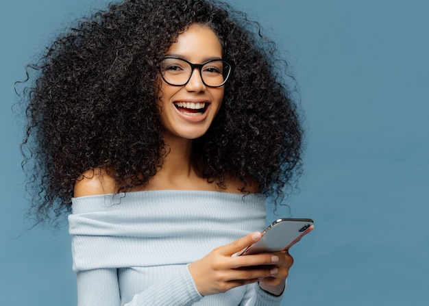 Curly cheerful woman with pleased expression, holds mobile phone, checks email box, wears optical glasses and jumper, enjoys using modern technologies
