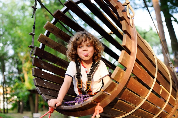 A curly child in climbing safety equipment in a tree house or in a rope park climbs the rope.