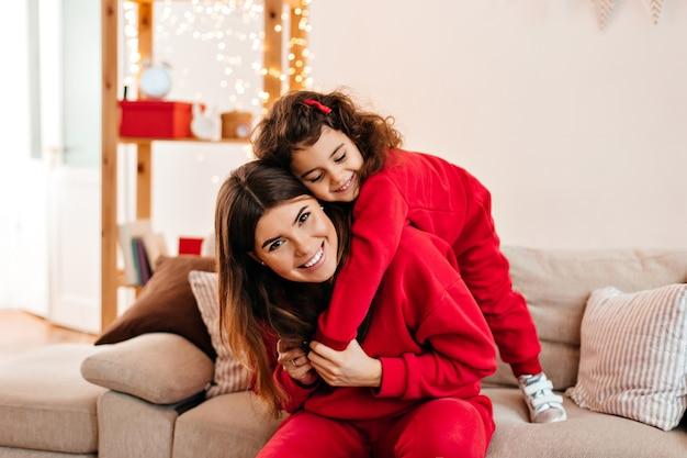 닫힌 된 눈으로 웃 고 어머니를 껴 안은 곱슬 아이. 엄마와 함께 연주 사랑스러운 초반 이었죠 아이의 실내 촬영.