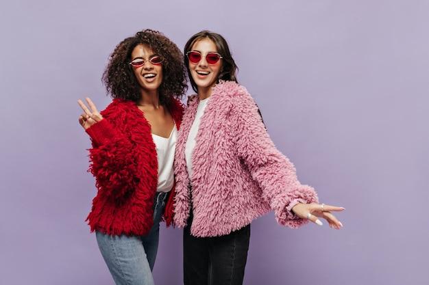 Кудрявая крутая девушка в солнечных очках в красном пушистом свитере и джинсах, знак мира и позирует с современной девушкой в розовой одежде на сиреневой стене