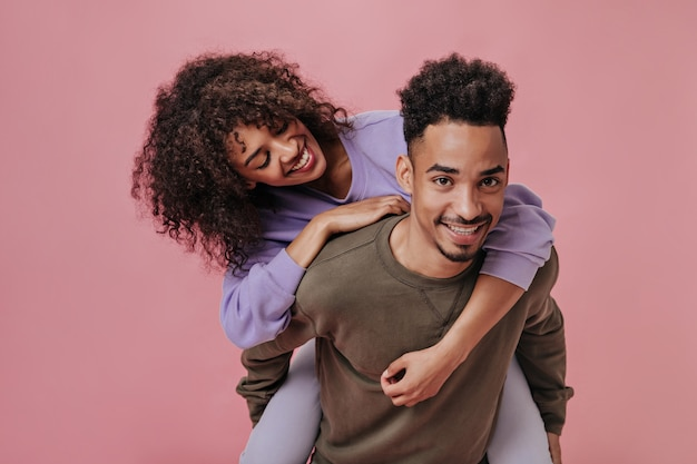 Curly couple smiling and having fun on pink wall