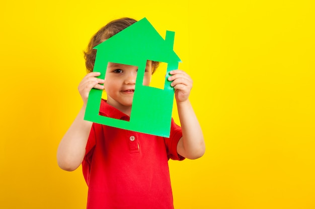 Curly cute baby holds a green cardboard house in hands