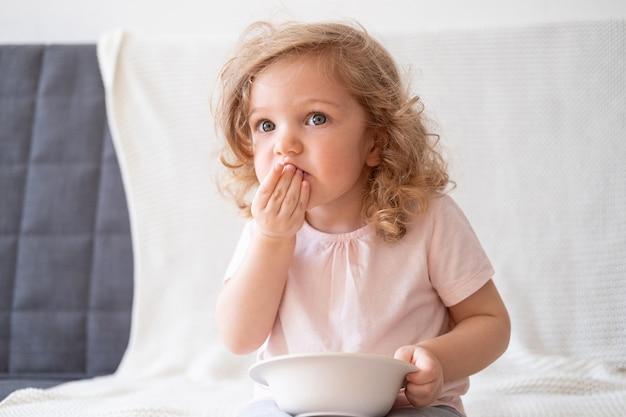 健康的な食べ物を食べる巻き毛のかわいい美しい女の赤ちゃん。有機製品とビタミンを使った健康的なライフスタイルのコンセプト。