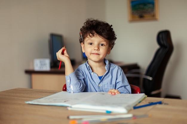 Кудрявый милый ребенок занимается обучением дома после школы