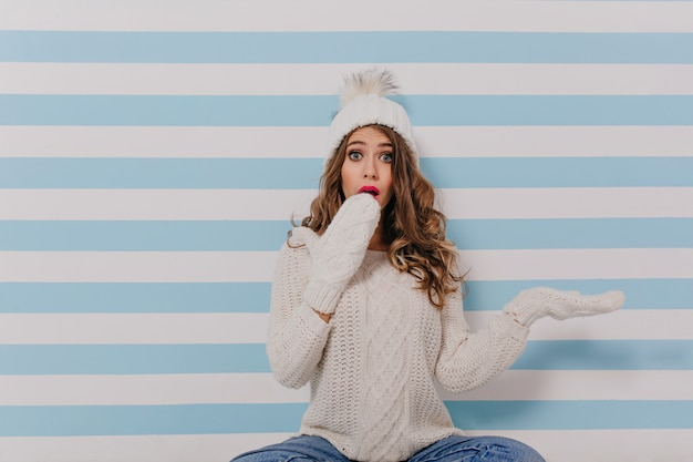 Curly dark blond girl in surprise covers face with her hands. portrait of lady in white knitted sweater