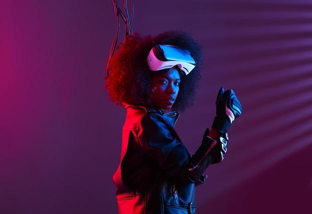 黒い革のジャケットと手袋を身に着けた巻き毛の暗い髪の少女は、ネオンライトのある暗いスタジオで彼女の頭にバーチャルリアリティメガネをかけています。サイバーパンクキャラクター