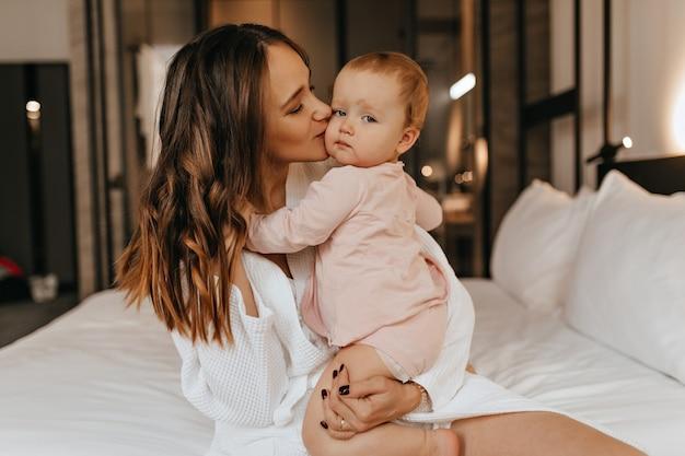 巻き毛の黒髪の女性は愛情を込めて彼女の小さな娘にキスします。白衣を着た若い母親と寝室での彼女の子供のショット。