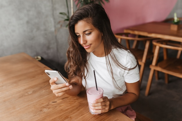 Curly dark-haired woman in white t-shirt writes message in phone and holds milkshake while sitting in cafe