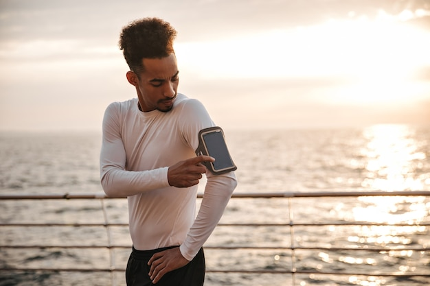 Curly dark-skinned cool man in white long-sleeved t-shirt and black shorts taps on phone screen and works out near sea