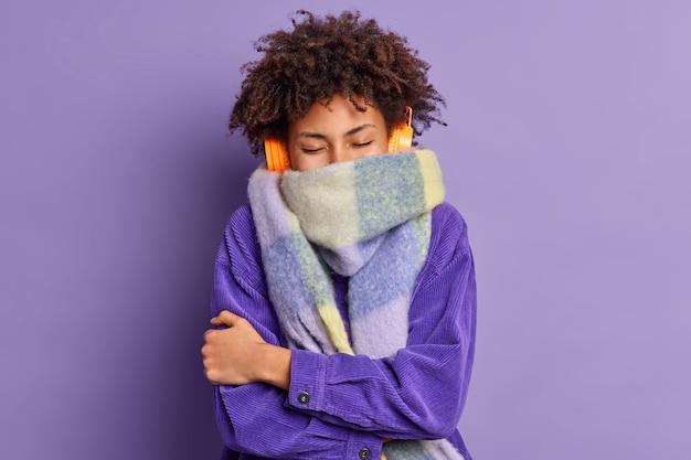 곱슬 곱슬 한 민족 십대 소녀는 추운 날씨에 재킷을 입고 목 주위의 따뜻한 스카프를 착용하고 선명한 보라색 벽에 자신의 몸 포즈를 포용하면서 음악을 즐기면서 자신을 따뜻하게하려고합니다.