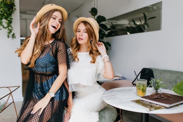 カーリーファッショナブルな女の子は、友人と時間を過ごしながらカフェでポーズをとってエレガントなジュエリーを身に着けています