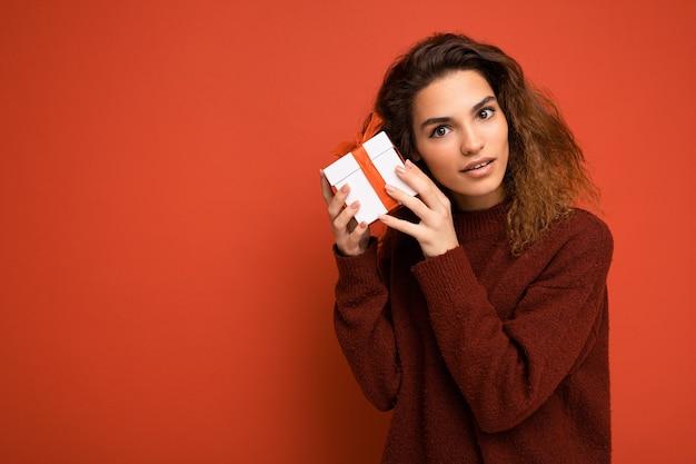 빨간색 배경 위에 절연 곱슬 여성 사람 카메라를 찾고 선물 상자를 들고 빨간 스웨터를 입고 벽. 자유 공간