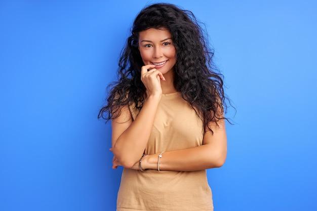 青で隔離の巻き毛の女性スタンド笑顔の口に触れる