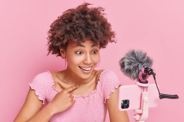 Curly female vlogger records broadcast at home points at herself and asks who me has online chat with subscribers streams live video smiles positively in camera isolated over pink