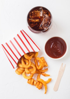 Curly fries fast food snack in paper container with glass of cola and ketchup on kitchen. unhealthy junk food