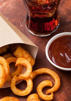 Curly fries fast food snack in paper container with glass of cola on rusty kitchen. unhealthy junk food