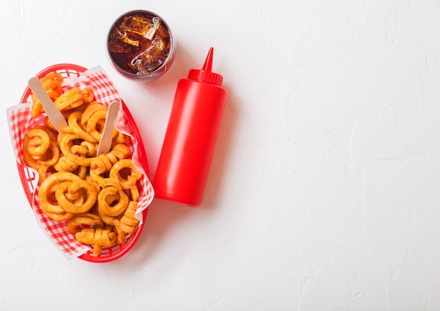 Curly fries fast food snack in red plastic tray with glass of cola and ketchup on kitchen. unhealthy junk food