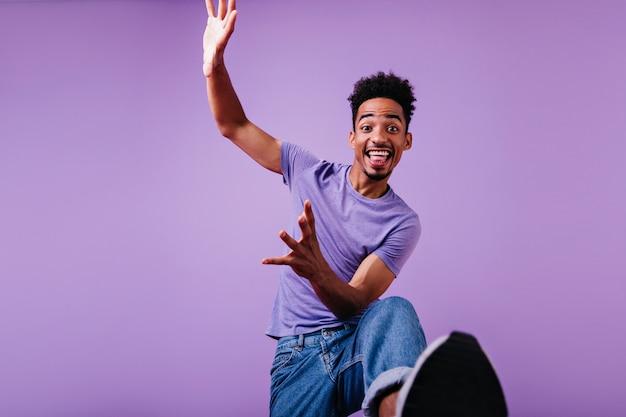 巻き毛の面白い男性モデルがジャンプして笑っています。 tシャツとジーンズのダンスでうれしそうな若い男。