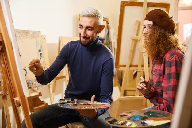 Кудрявая девушка и мужчина рисуют картину и улыбаются