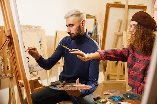 Кудрявая девушка и мужчина рисуют картину