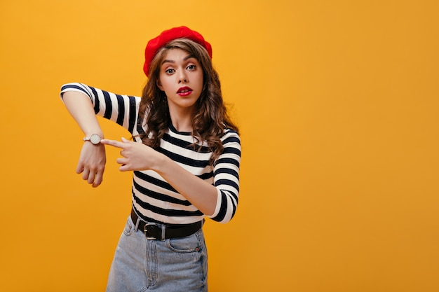 Ragazza riccia in berretto che indica il suo orologio. moderna giovane donna con capelli ondulati in maglione a righe in posa su sfondo isolato.