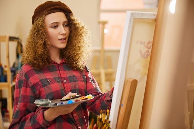 La ragazza riccia disegna una foto con colori ad olio e un pennello