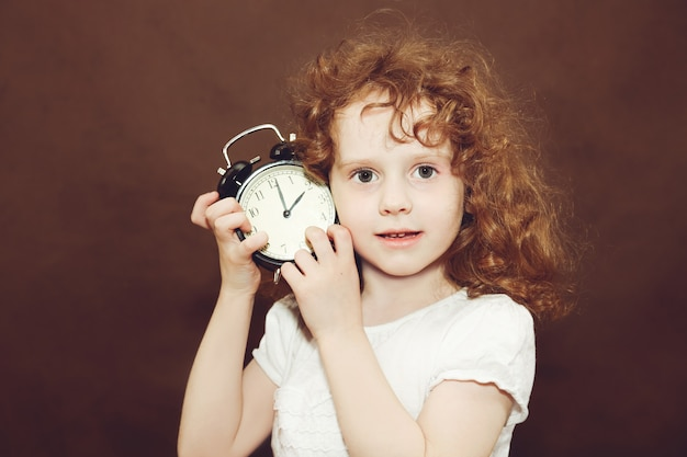 Curly girl holding alarm clock. photo toned brown.