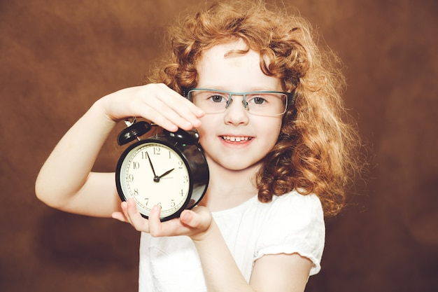 Curly girl holding alarm clock.