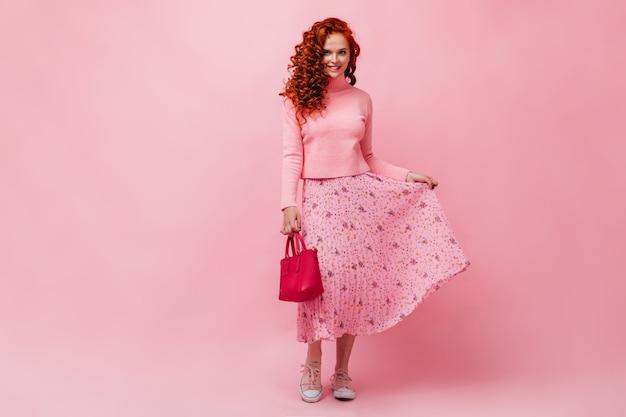 明るいバッグとミディスカートの裾を持った巻き毛の女の子