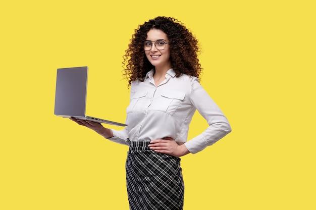 노란색 배경 위에 절연 노트북 컴퓨터를 들고 안경과 흰 셔츠에 곱슬 소녀