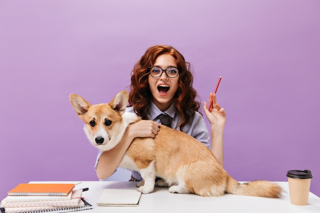 셔츠와 안경에 곱슬 소녀는 개를 안고 연필을 보유하고 있습니다.