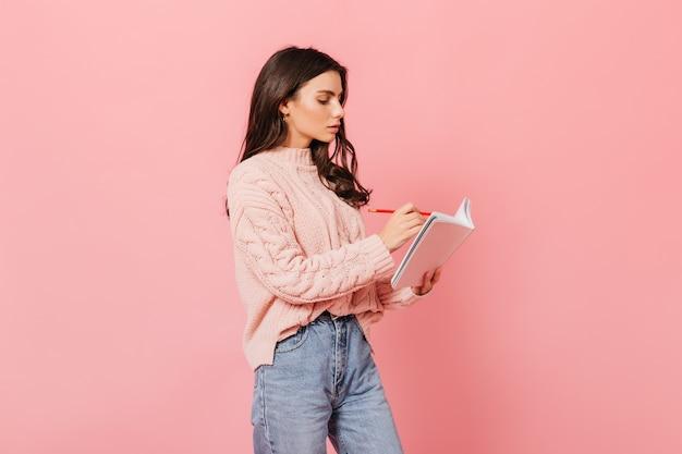 Кудрявая девушка внимательно делает записи в дневнике. женщина в свитере позирует на розовом фоне.