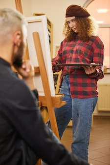 Curly girl is drawing and looks at a man sits before her