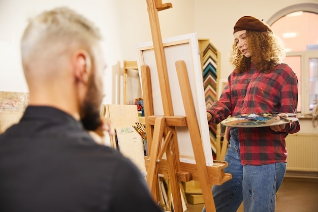Curly girl is drawing a portrait of a man sits before her