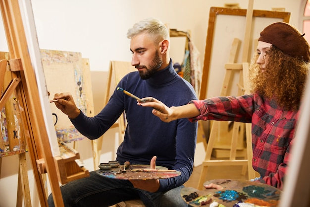Curly girl and man draw a painting