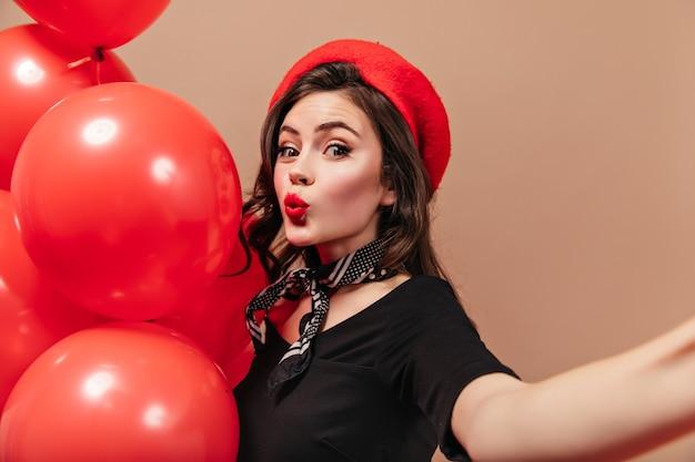 Ragazza riccia in berretto rosso e sciarpa di seta fischia, tiene palloncini e fa selfie.