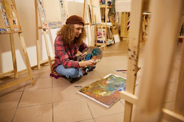 Кудрявая девушка сидит на полу и рисует картину маслом