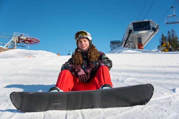 Curly girl sitting with snowboard in snow near ski lift