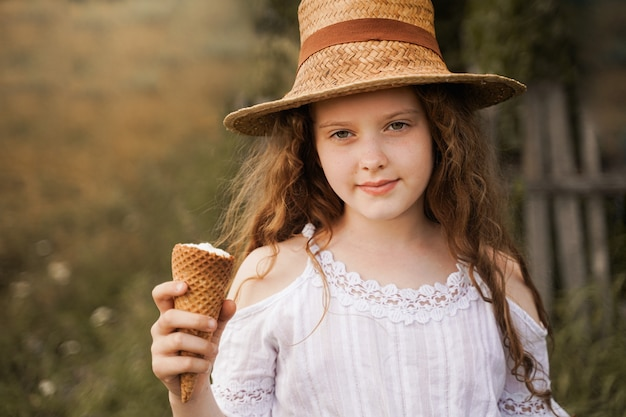 Curly girl in a straw hat eats ice cream in the village in the summer