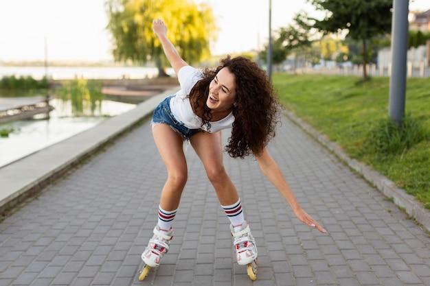 Кудрявая девушка гуляет со своими роликами