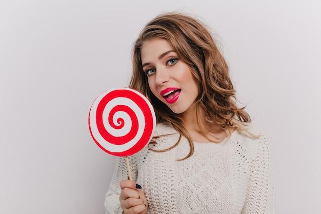 Кудрявая девушка с серыми глазами хочет съесть огромный бело-красный леденец, позирует на изолированной стене
