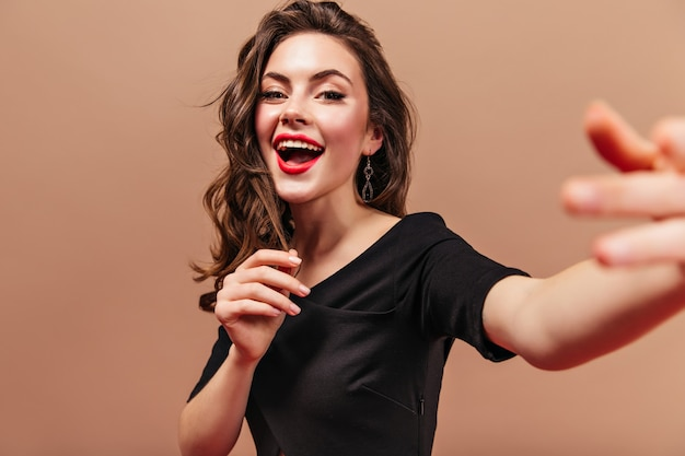 Curly girl with red lips dressed in black top makes selfie on beige background.