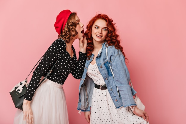 Curly girls in casual outfit talking on pink background. studio shot of refined friends sharing rumours.